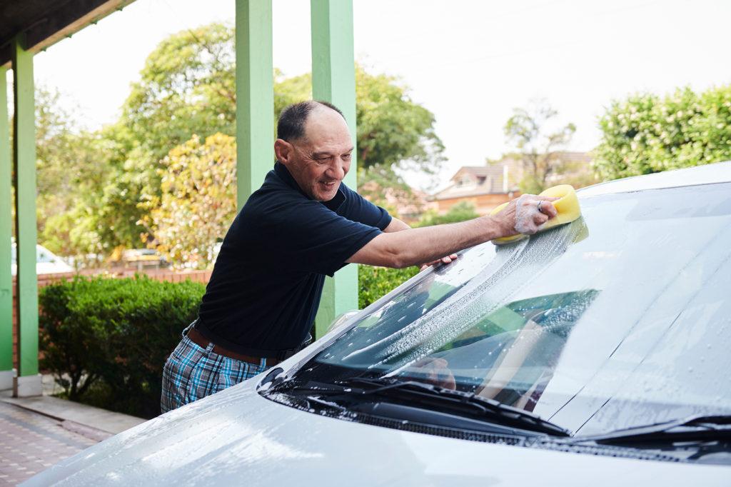 Guy in blue shirt washing car outside