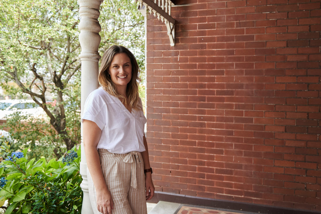 Lady in white top and pants on front porch