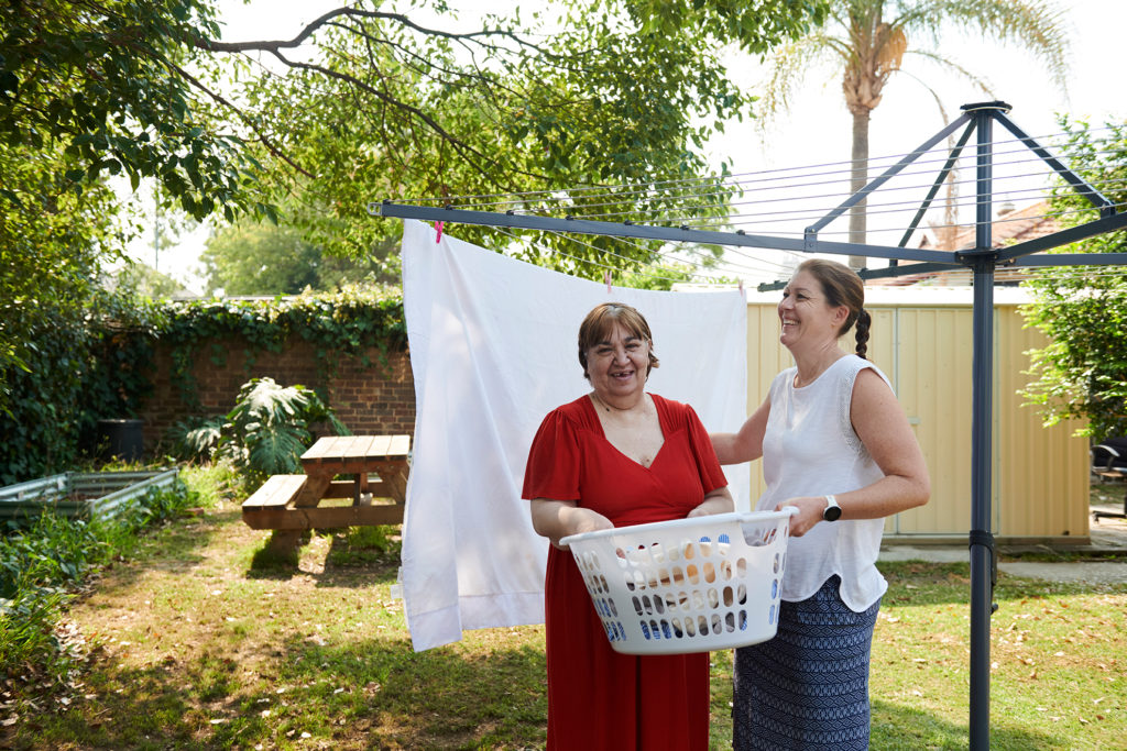 lady in red with carer outside at washing line