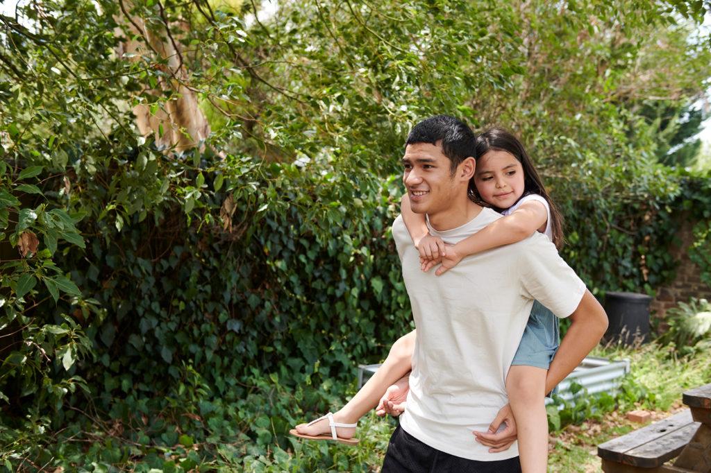 Youth piggybacking girl in garden