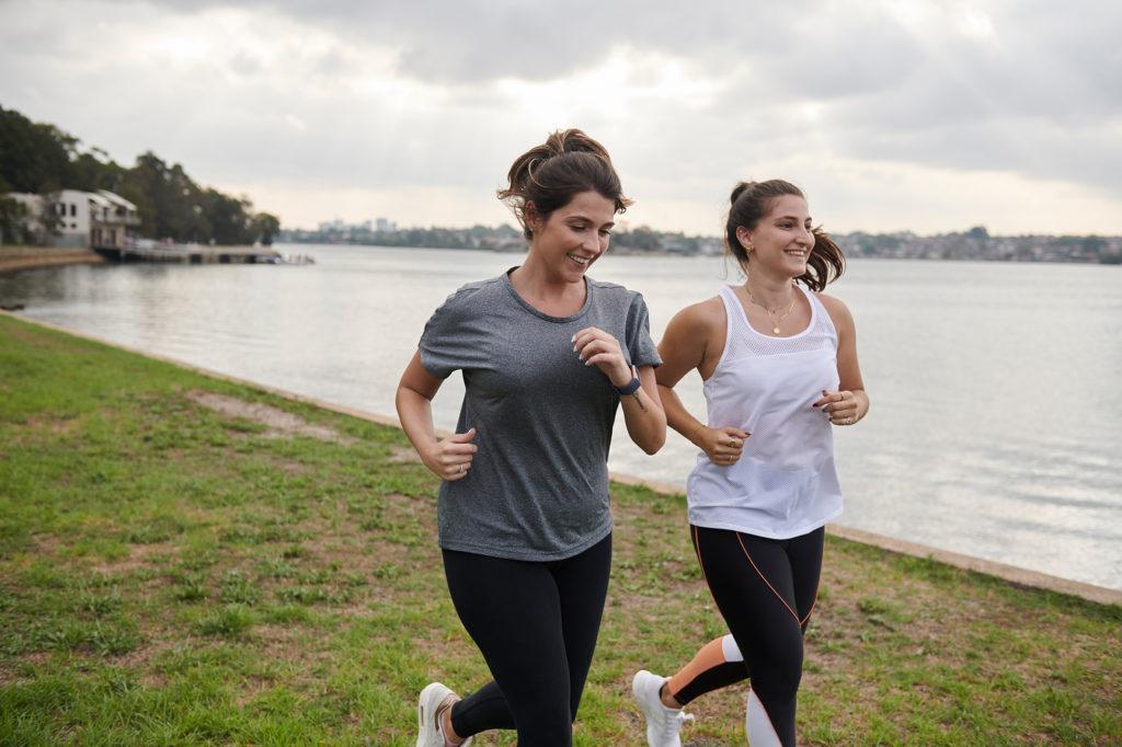 2 girls running along the shoreline