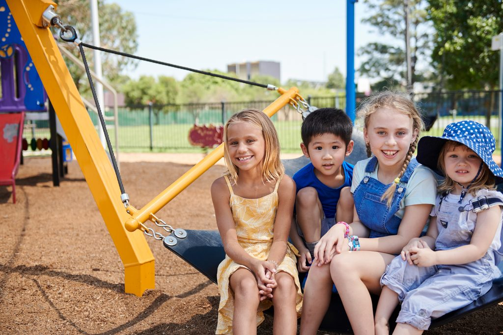 young children sitting in a playground