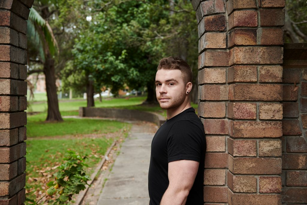 Guy in black t-shirt leaning against a wall outside