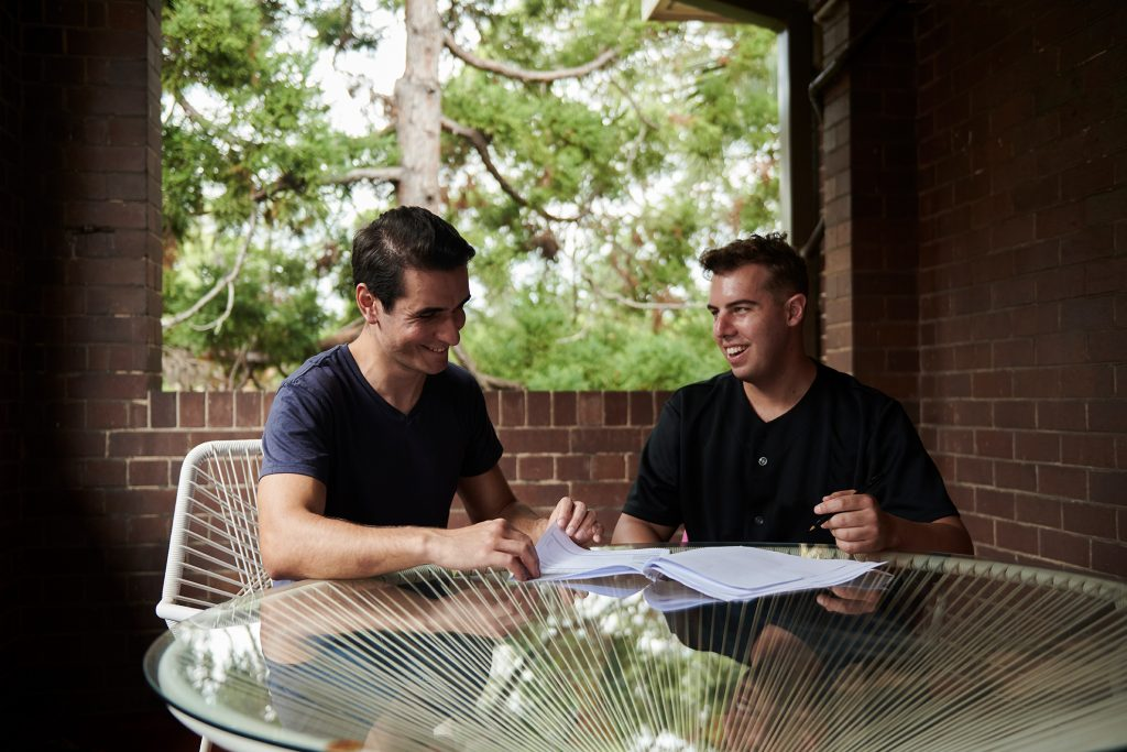 Male carer and client at outside table with document