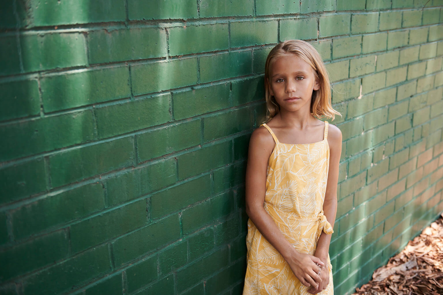 Young girl next to wall