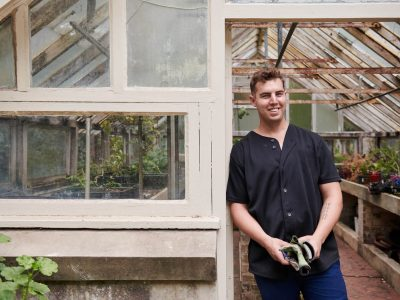 man standing next to greenhouse